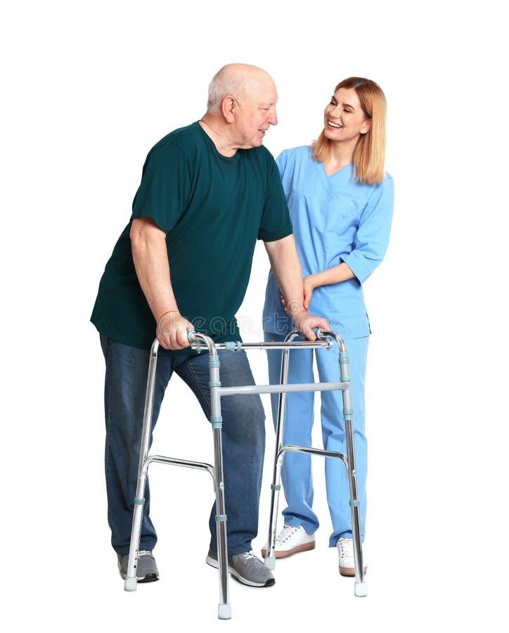 Dozorca starszych osob pomaga mężczyzna z odprowadzenie ramą na bielu zdjęcie stock