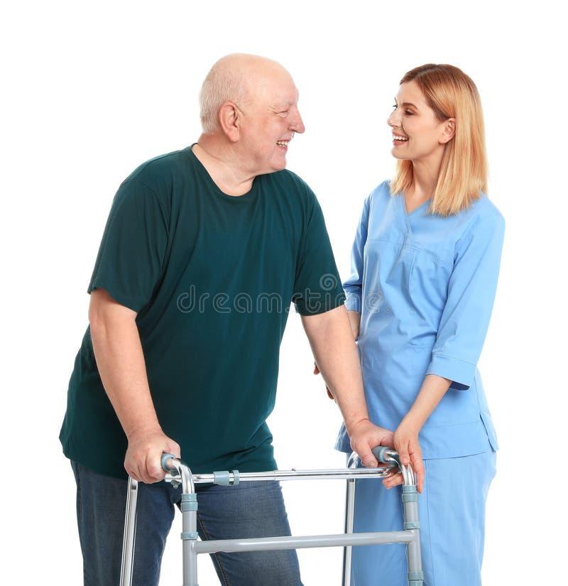 Dozorca starszych osob pomaga mężczyzna z odprowadzenie ramą na bielu fotografia stock