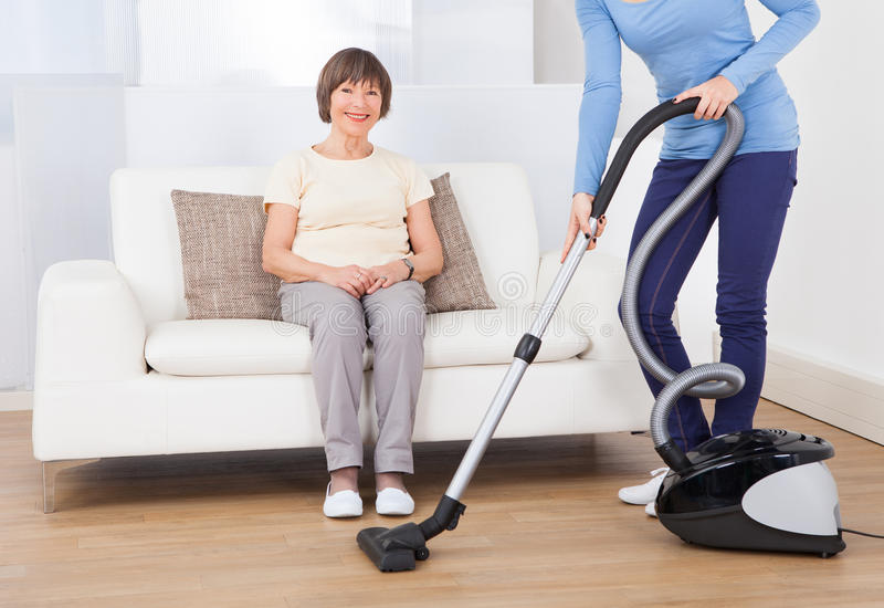 Dozorcy cleaning podłoga podczas gdy starszy kobiety obsiadanie na kanapie fotografia stock