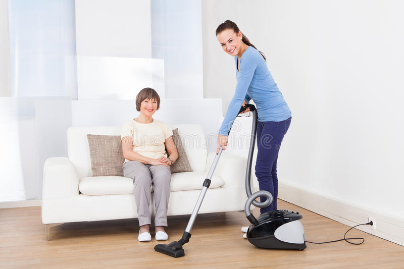 Dozorcy cleaning podłoga podczas gdy starszy kobiety obsiadanie na kanapie zdjęcie stock