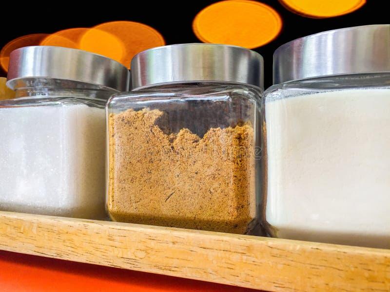 Dozzina vetri di zucchero bianco, di zucchero bruno e di crema artificiale per il riempimento nella bevanda calda fotografia stock