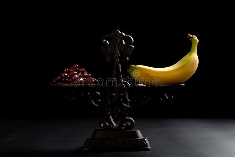 Dozzine di capsule e una banana su un concetto equilibrato della scala di cibo sano fotografie stock