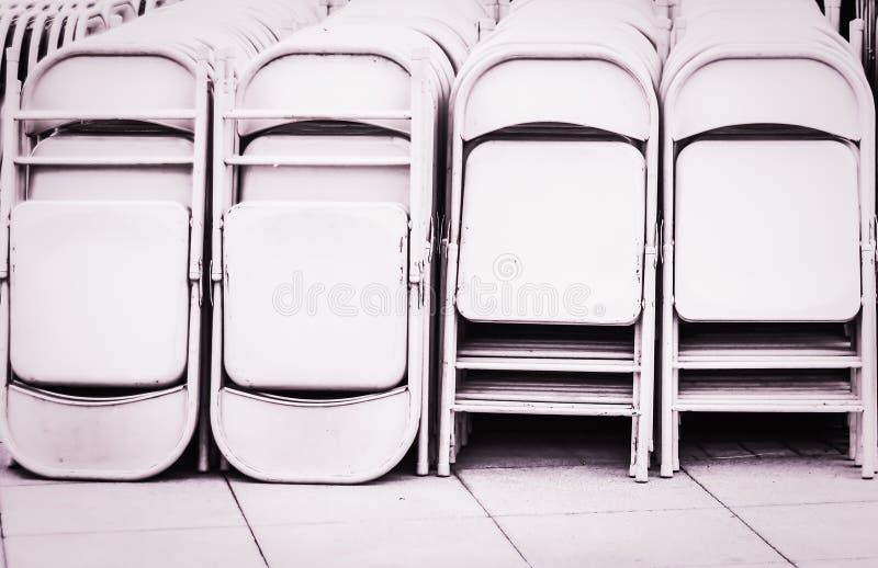 Dozzine piegare le sedie del metallo bianco impilate Partito esterno immagini stock