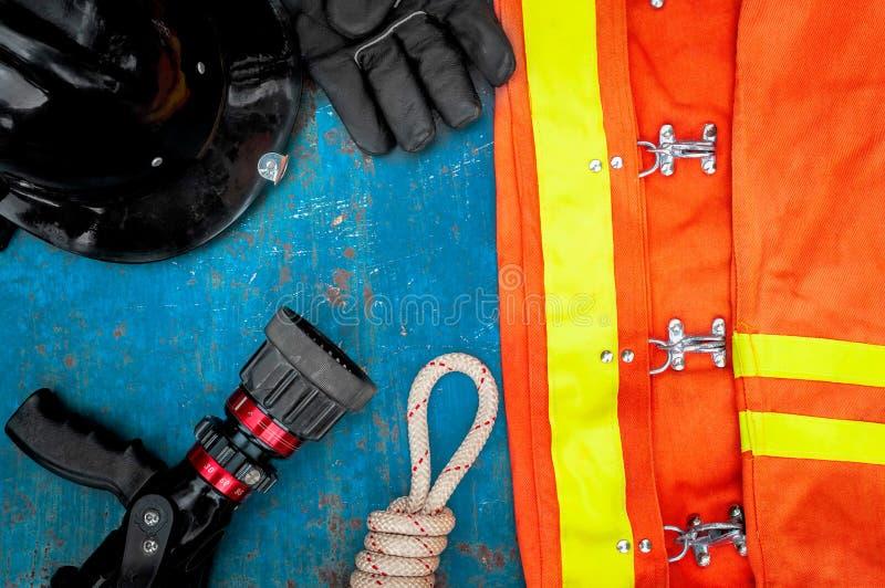 Dräkt av brandmannen som förläggas på gammal tabellbakgrund fotografering för bildbyråer