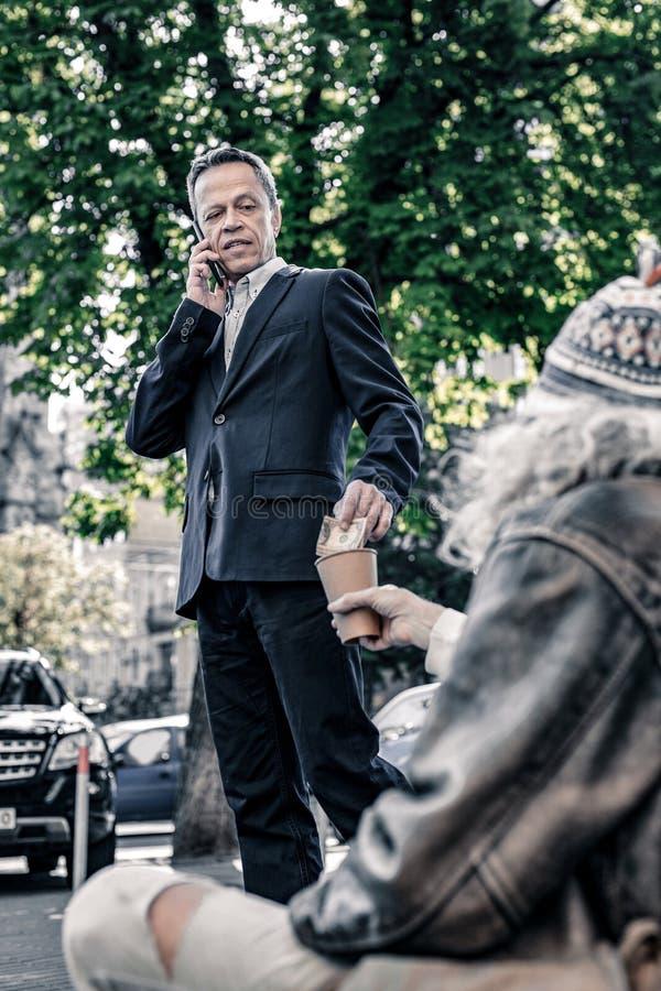 Dräkt för affär som i regeringsställning talar på smartphonen och hjälpande arbetslös man arkivbilder