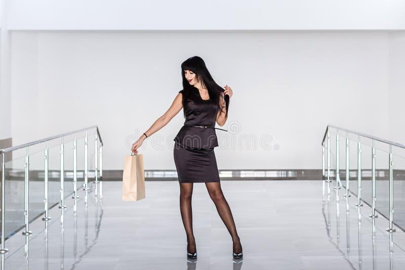 Dräkt för affär för ung härlig lycklig brunettkvinna som iklädd svart rymmer den pappers- shoppa påsen som går på en galleria royaltyfria bilder