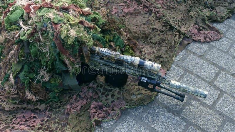 Dräkt för kamouflage för förklädnad för arméprickskytt bärande på den militära showen arkivfoto