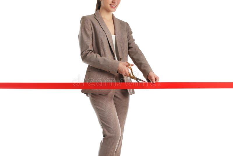 Dräkt för kvinna som i regeringsställning klipper det röda bandet, closeup arkivbild