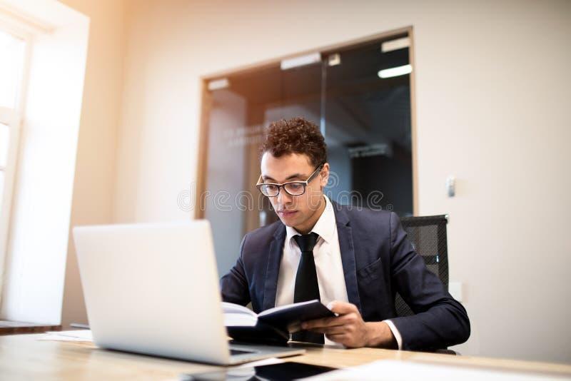 Dräkt och exponeringsglas för kompetent företagsägare för man som iklädd officiell läser från information om lärobok om datum av  arkivbild