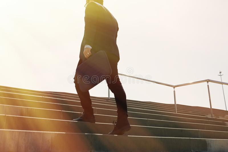 Dräkt och spring för ung förtrolig affärsman snabba bärande uppför trappan Horisontaldet friaskott solig effekt arkivfoton