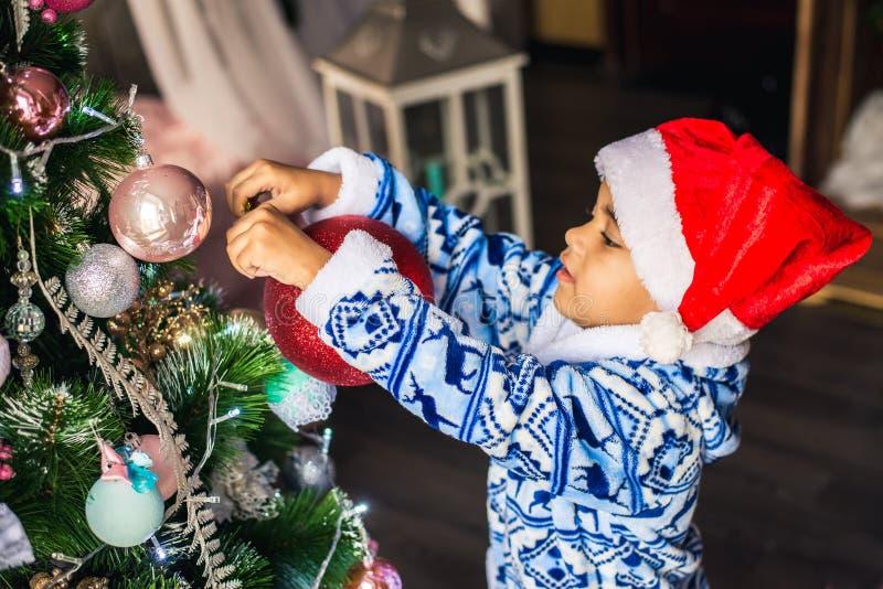 Dräkt Santa Claus som för afrikansk amerikanpojkepåklädd dekorerar en julgran arkivfoton