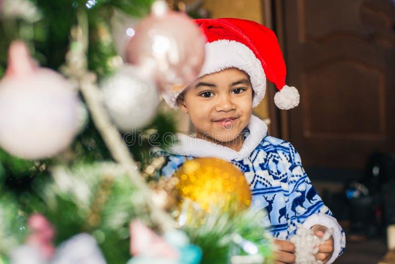 Dräkt Santa Claus som för afrikansk amerikanpojkepåklädd dekorerar en julgran royaltyfria foton