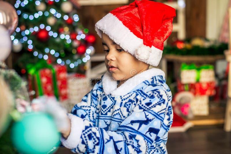 Dräkt Santa Claus som för afrikansk amerikanpojkepåklädd dekorerar en julgran royaltyfria bilder