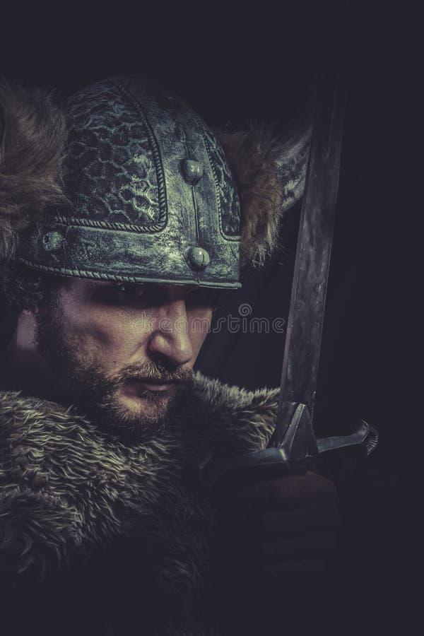 Dräkt-, Viking krigare med ett enormt svärd och hjälm med horn arkivfoton