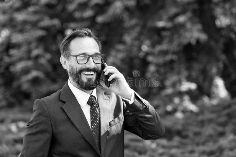 Dräkten och exponeringsglas för attraktiv lycklig yrkesmässig affärsman som parkerar den iklädda talar på mobiltelefonen utanför  arkivbilder