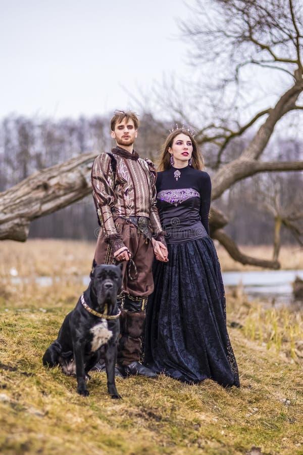 Dräktlek Par som riddaren Warrior och prinsessa med den svarta hunden som poserar i medeltida kläder i våren Forest Outdoors royaltyfri bild