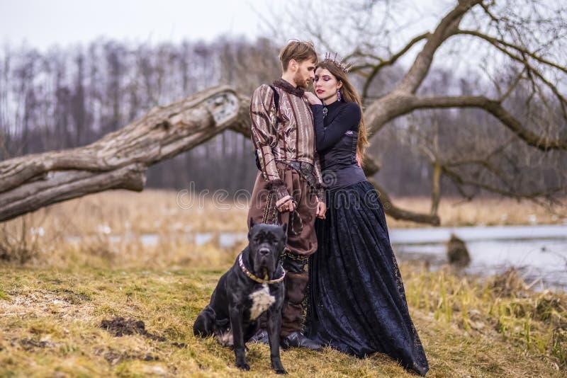 Dräktlek Par som riddaren Warrior och prinsessa med den svarta hunden som poserar i medeltida kläder i våren Forest Outdoors arkivbild