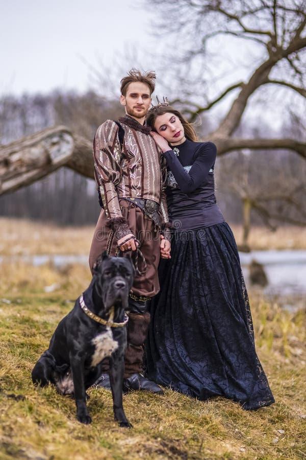 Dräktlek Par som riddaren Warrior och prinsessa med den svarta hunden som poserar i medeltida kläder i våren Forest Outdoors arkivfoto