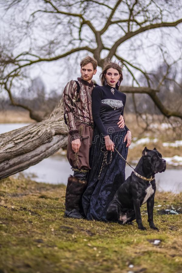 Dräktlekprojekt Par som riddaren Warrior och prinsessa med den svarta hunden som poserar i medeltida kläder i våren Forest Outdoo royaltyfri foto