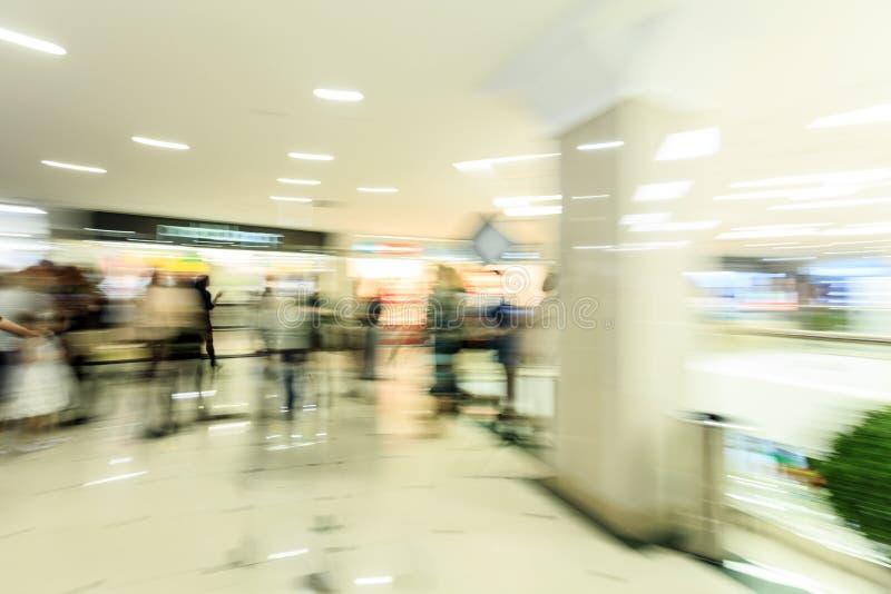 Drängen Sie das Hetzen innerhalb einer modernen breiten hellen Mallhalle mit Butiken, Glasanzeigenfenster, Leute in der Bewegungs stockfotos