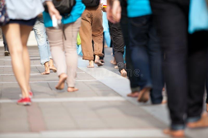 Drängen Sie sich, durch Bärnfüße auf Fußweg mit Rucksack hinter ihre Rückseite an gehen bewegend lizenzfreie stockfotos