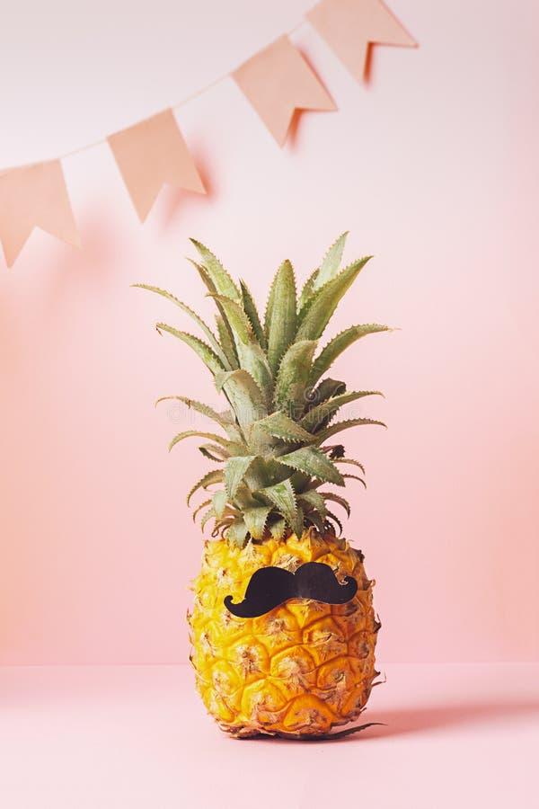 Dr?le habill? vers le haut de l'ananas avec un fond en pastel de rose noir de moustache avec les drapeaux de f?te minimalisme Cad photographie stock