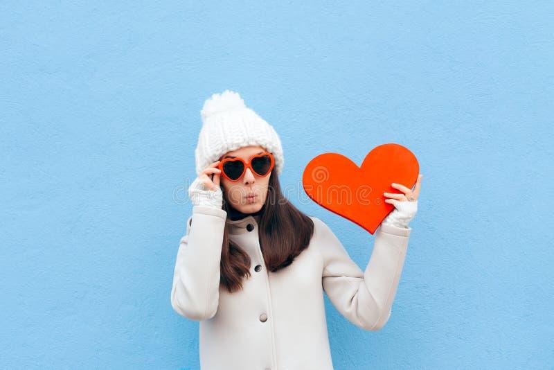 Drôle mignon dans la fille d'amour tenant le grand coeur sur le fond bleu photographie stock libre de droits