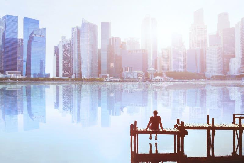 Dröm- begrepp, mansammanträde på pir och tycka om modern cityscape arkivbilder