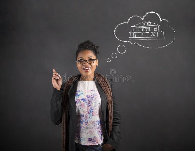 Dröm- hus för afrikansk idé för kvinna bra på svart tavlabakgrund arkivfoton