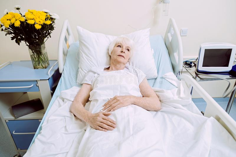 Drömlik äldre kvinna i sjukhussäng som tänker om något royaltyfri bild