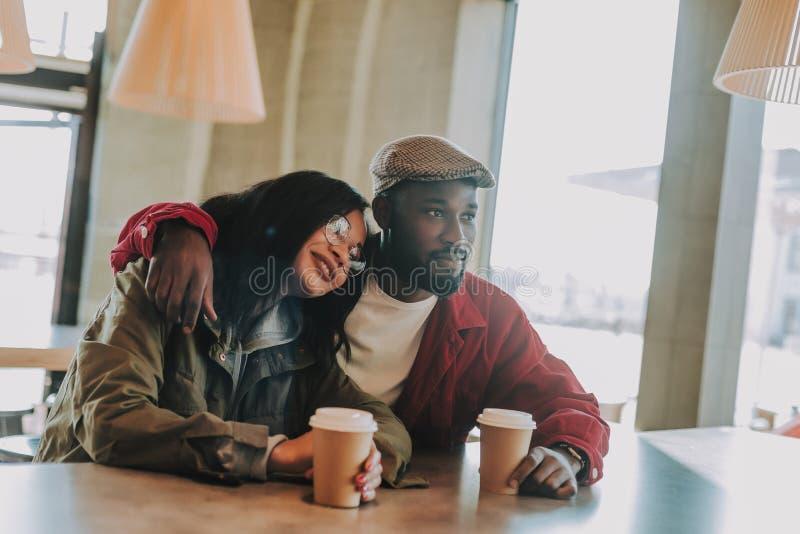 Drömlik dam som sätter huvudet på skuldran av hennes pojkvän och kopplar av i kafé royaltyfri foto