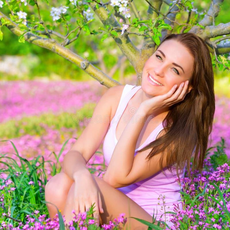 Drömlik flicka i vårträdgård royaltyfri fotografi