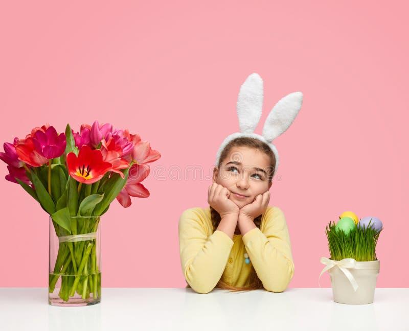 Drömlik flicka nära påskägg och blommor royaltyfri bild