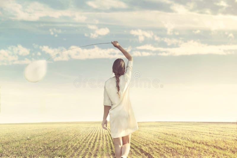 Drömlik kvinna som går in mot oändlighet med hennes vita ballong royaltyfria bilder