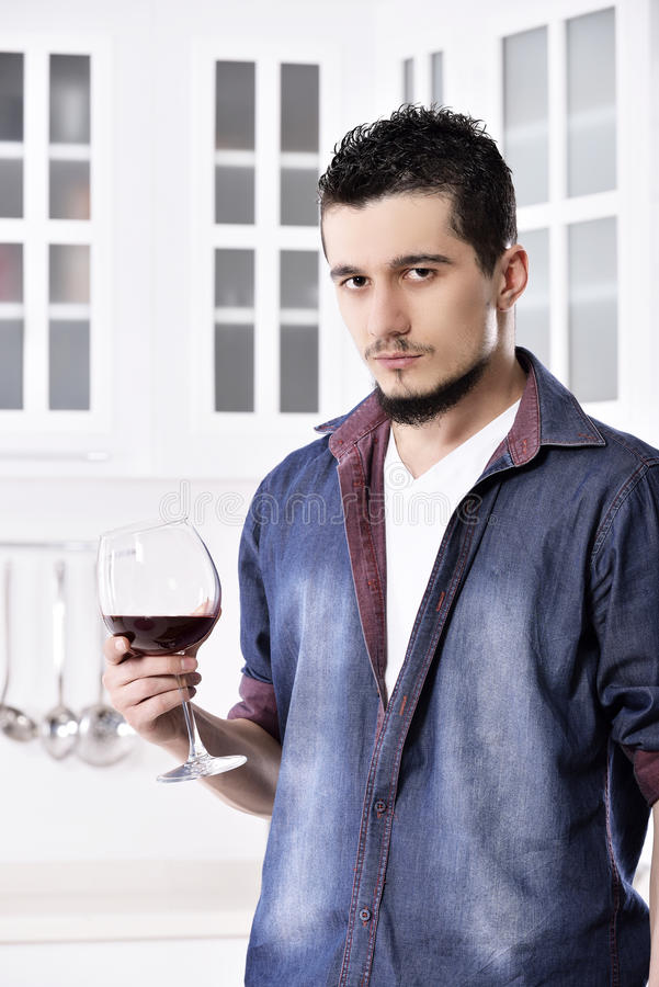 Drömlik lycklig väl seende man som dricker rött vin i köket arkivfoto