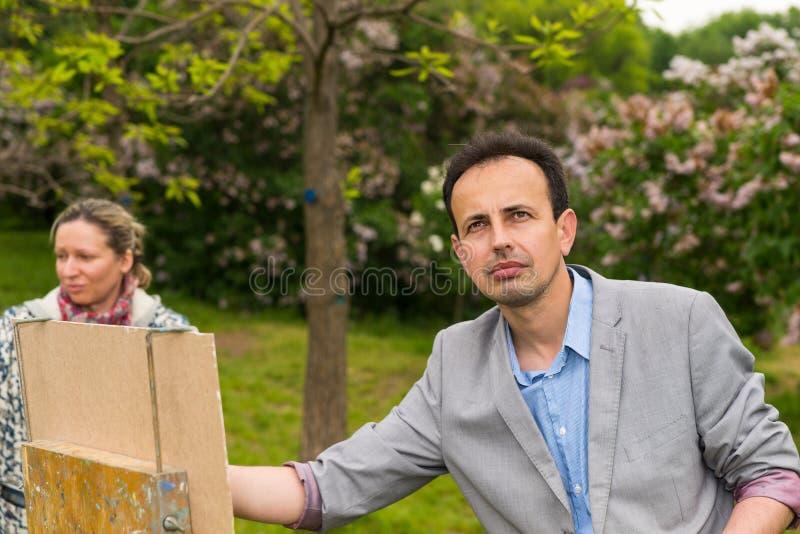 Drömlik manlig målare- och kvinnligkonstnär under konstgrupp utomhus royaltyfria foton