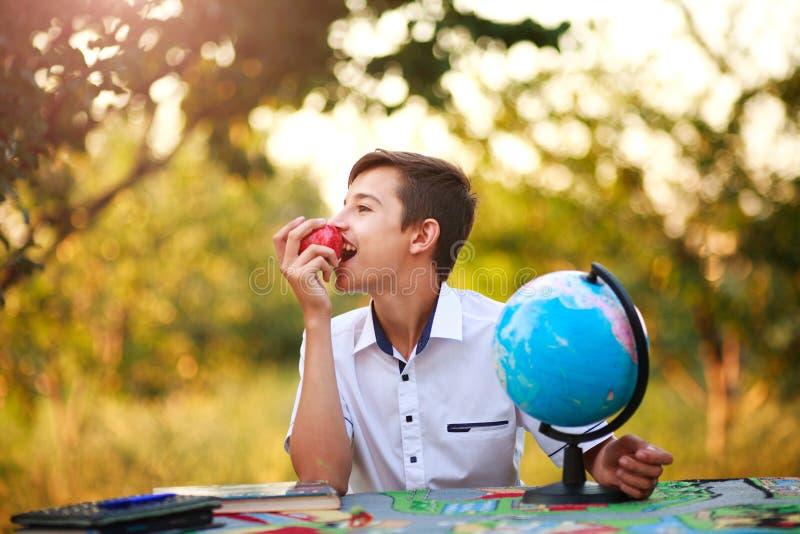 Drömlik pojkestudenttonåring på tabellen med äpplet och jordklotet royaltyfri bild