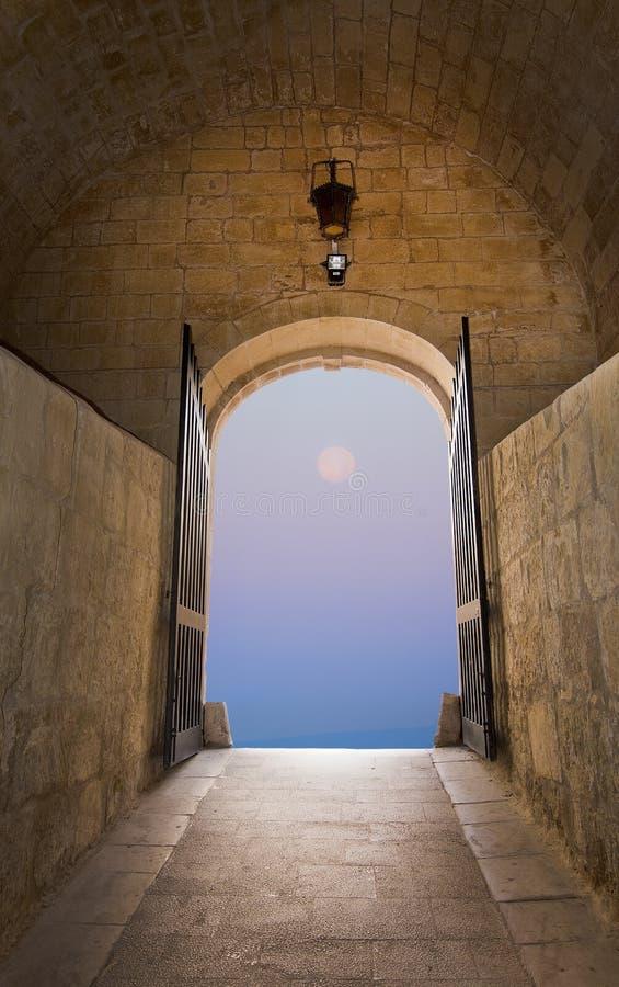 Drömlik purpurfärgad fullmånehimmel till och med portarna av medeltida sagaportar arkivfoton
