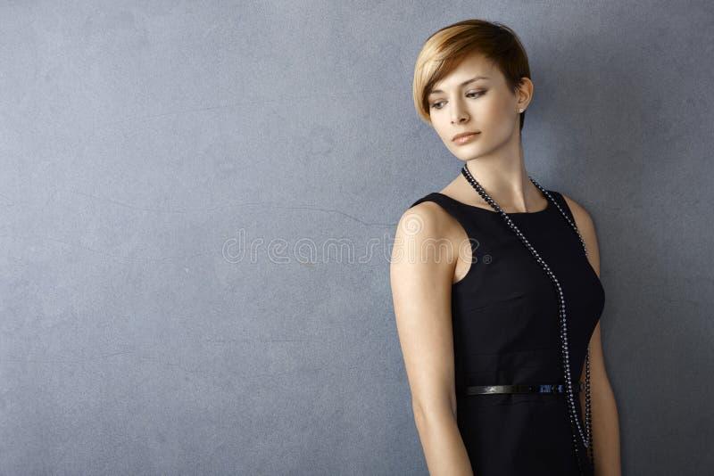 Drömlik ung kvinna i svart klänning royaltyfria bilder