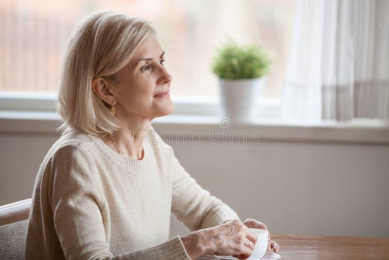 Drömlikt åldrigt kvinnligt tyckande om te som minns angenäma minnen royaltyfri bild