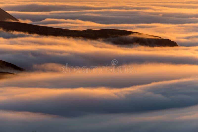 Drömlikt dimmigt landskap ovanför havet av moln, berg på solnedgången i Island arkivbild