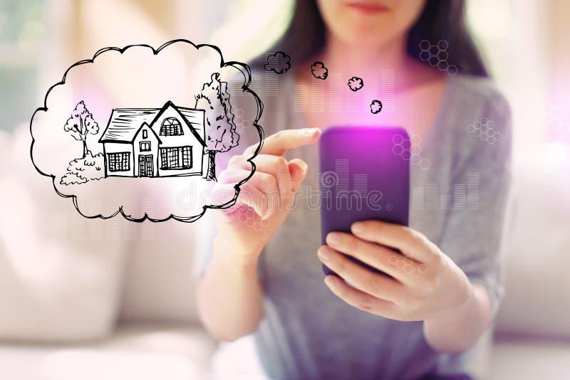Drömma av det nya hemmet med kvinnan som använder en smartphone arkivbilder