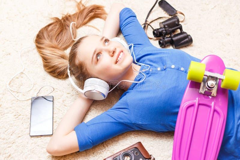 Drömma den gladlynta tonårs- flickan som ligger på golvet royaltyfria foton