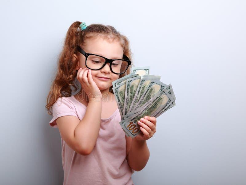 Drömma den gulliga ungeflickan som ser på pengar och tänker hur kan spendera arkivbilder
