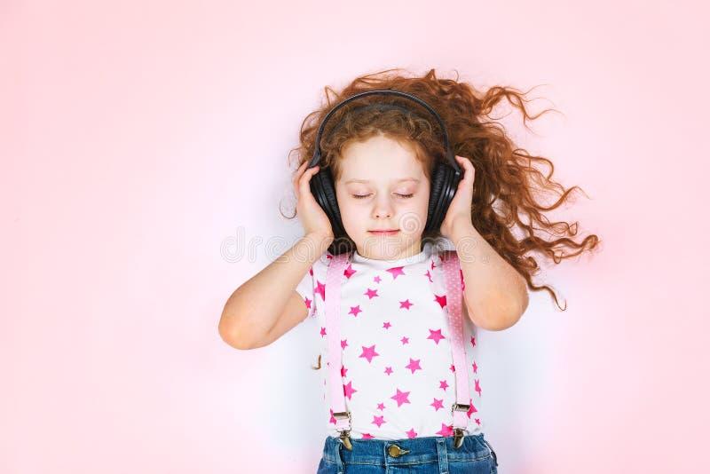 Drömma den lockiga flickan som lyssnar till musik med hörlurar arkivbilder