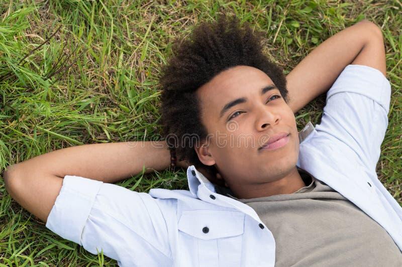 Drömma den unga afrikanska mannen royaltyfri bild