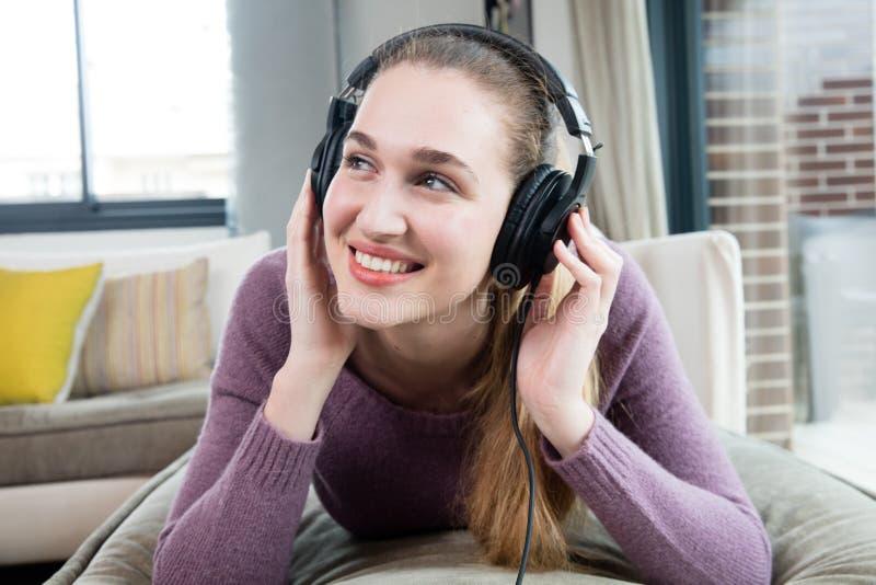Drömma den ursnygga flickan som ner ligger och att tycka om att lyssna till avslappnande musik arkivfoton