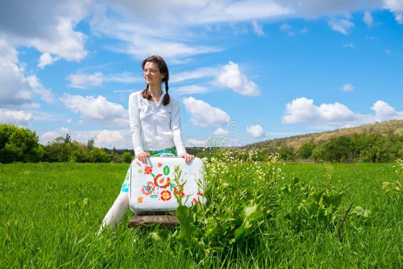 Drömma flickaanseende i grönt fält på molnbakgrund arkivbilder