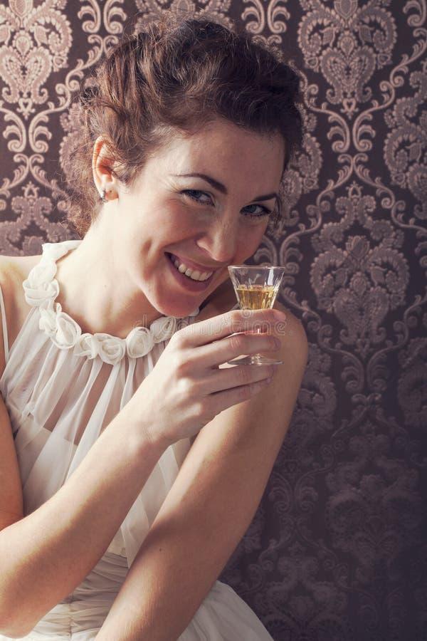 Drömma kvinnan dricker ett exponeringsglas av utmärkt skotsk whisky arkivfoton