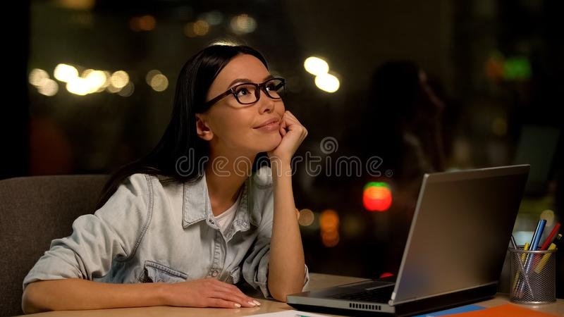Dr?mma kvinnan som sitter den fr?mre b?rbara datorn som ?r tr?tt av tr?kigt arbete, fr?nvarande anst?lld royaltyfria bilder